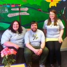 Photograph of 3 staff with cafe mural in the background