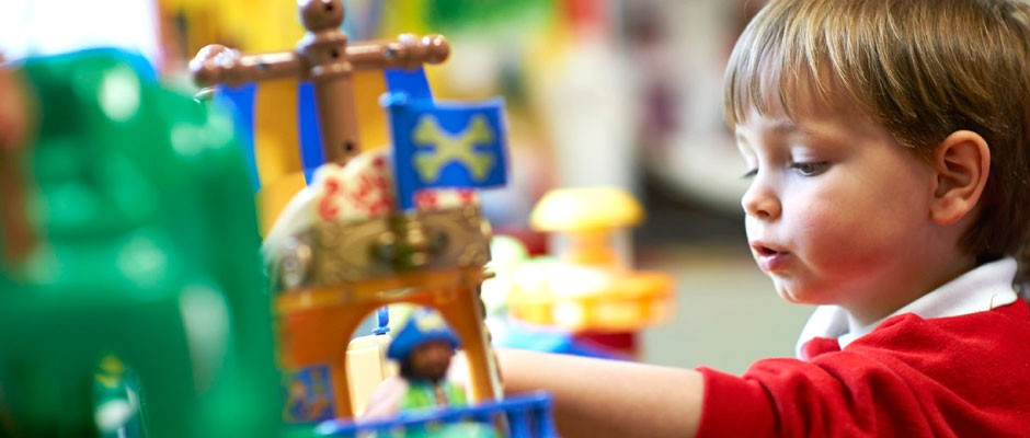 Young Child in Lots of Tots Nursery playing with pirate ship