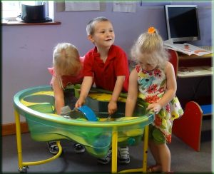 Photograph of Lots of Tots children playing in the indoor sandpit